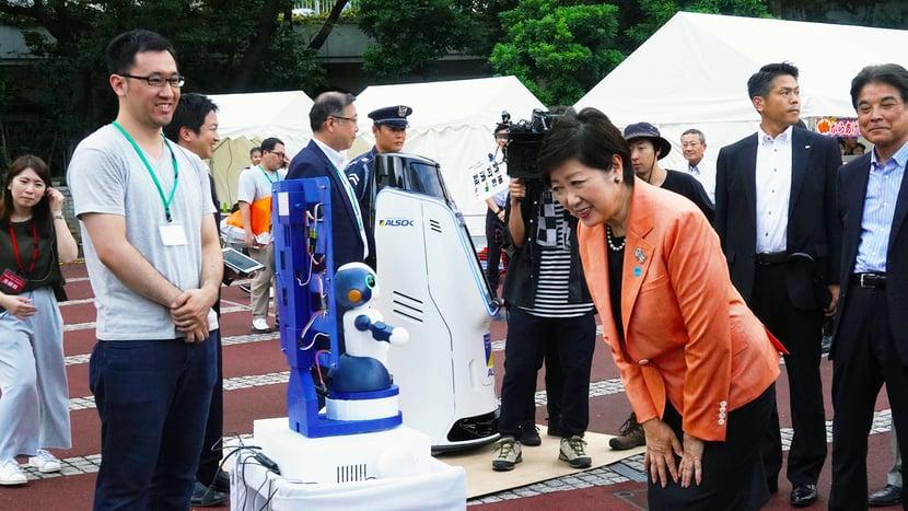 説明:コミュニケーションロボットの実証実験。写真中央は、小池百合子東京都知事。