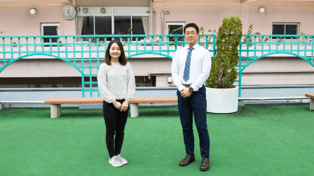 本卒業イベントの立案者で「ピグパーティ」プランナーの石橋(写真左)と、品川女子学院の白石先生(写真右)。2020年卒業生の学年主任をされていた白石先生のご協力のもと、本企画が実現した。今回のイベントエリアにもなった、品川女子学院の中庭にて。